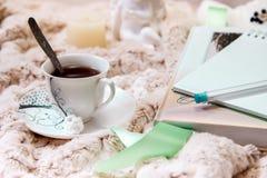 Книга, тетрадь, чашка черного кофе, арахисов в сахаре, свече, статуе ангела от гипсолита на мягком, бежевом одеяле стоковые изображения