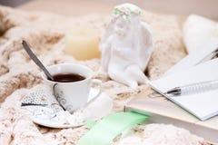 Книга, тетрадь, чашка черного кофе, арахисов в сахаре, свече, статуе ангела от гипсолита на мягком, бежевом одеяле стоковые фотографии rf
