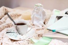 Книга, тетрадь, чашка черного кофе, арахисов в сахаре, свече, статуе ангела от гипсолита на мягком, бежевом одеяле стоковое фото