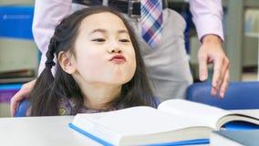 Книга усаживания и чтения девушки Smiley азиатская милая на таблице Стоковая Фотография RF