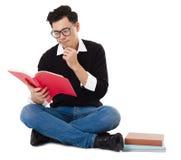 Книга усаживания и чтения молодого человека стоковая фотография