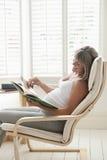 Книга чтения беременной женщины на стуле Стоковые Изображения