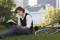 Книга чтения бизнесмена велосипедом в парке Стоковые Изображения