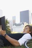 Книга чтения бизнесмена в парке города Стоковые Изображения RF