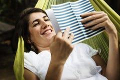 Книга чтения взрослой женщины на гамаке Стоковое Изображение RF