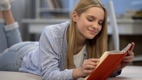 Книга чтения девочка-подростка, мечтающ романтичной влюбленности, представляющ героикоромантического человека стоковое фото rf