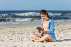 Книга чтения девочка-подростка сидя на пляже Стоковые Изображения