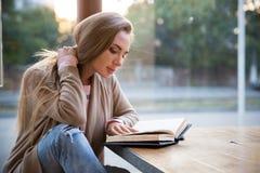 Книга чтения девушки в кафе Стоковые Изображения