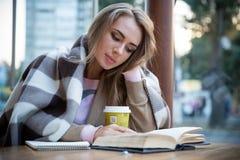 Книга чтения девушки в кафе Стоковая Фотография