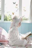 Книга чтения девушки в костюме единорога на кровати Стоковое Изображение RF