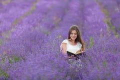 Книга чтения девушки в поле лаванды Стоковые Изображения RF