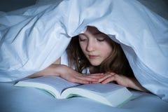 Книга чтения девушки в спальне Стоковое Изображение RF