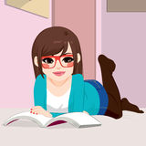 Книга чтения девушки лежа вниз Стоковое фото RF