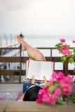 Книга чтения девушки на балконе с взглядом взморья Стоковое Изображение
