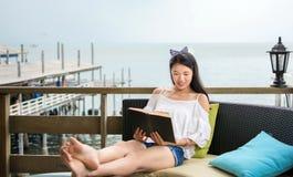 Книга чтения девушки на балконе с взглядом взморья Стоковые Изображения RF