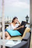 Книга чтения девушки на балконе с взглядом взморья Стоковая Фотография