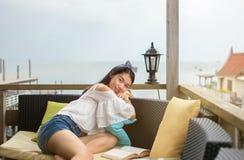 Книга чтения девушки на балконе с взглядом взморья Стоковое Фото