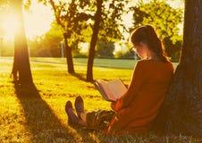 Книга чтения девушки на парке Стоковая Фотография