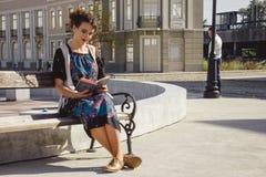 Книга чтения девушки на стенде в городке пока человек запасает в th Стоковые Изображения
