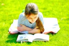 Книга чтения девушки на траве Стоковое фото RF