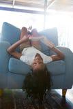 Книга чтения девушки пока лежащ на кресле дома Стоковое фото RF