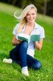 Книга чтения девушки сидит на зеленой траве стоковые изображения rf