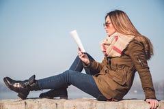 Книга чтения девушки снаружи на красивый день Стоковая Фотография