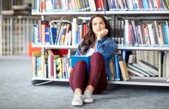 Книга чтения девушки студента средней школы на библиотеке Стоковая Фотография RF