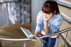 Книга чтения девушки студента средней школы на библиотеке Стоковые Изображения