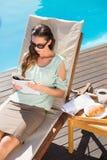 Книга чтения женщины бассейном с завтраком на таблице Стоковая Фотография