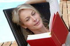 Книга чтения женщины бассейном Стоковая Фотография