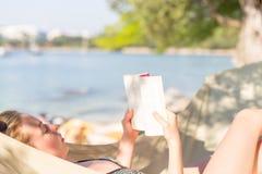 Книга чтения женщины в гамаке на пляже Стоковое Фото