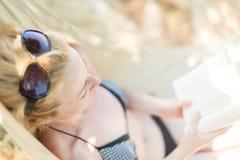 Книга чтения женщины в гамаке на пляже Стоковые Фото