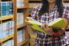 Книга чтения женщины в комнате библиотеки и предпосылке книжных полков, концепции образования стоковое фото rf