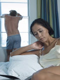Книга чтения женщины в кровати с человеком в предпосылке Стоковое Изображение