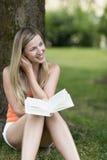 Книга чтения женщины в парке Стоковая Фотография RF