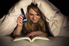 Книга чтения женщины держа факел Стоковые Фотографии RF