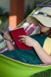 Книга чтения женщины на гамаке Стоковое фото RF