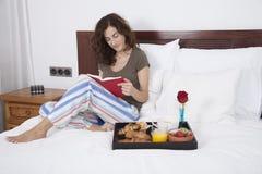 Книга чтения женщины на завтраке Стоковое Изображение RF
