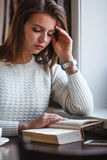 Книга чтения женщины на кафе около окна Стоковое фото RF