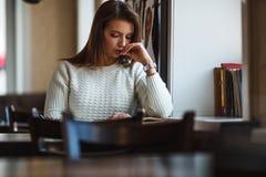 Книга чтения женщины на кафе около окна Стоковое Изображение RF
