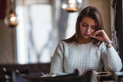 Книга чтения женщины на кафе около окна Стоковые Изображения RF