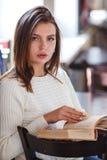 Книга чтения женщины на кафе около окна Стоковое Фото