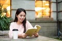 Книга чтения женщины на кафе Стоковая Фотография