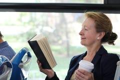 Книга чтения женщины на поезде или шине Стоковые Фотографии RF
