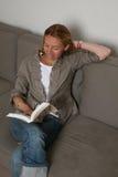 Книга чтения женщины на софе Стоковая Фотография
