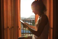Книга чтения женщины на спальне восхода солнца в утре Стоковые Изображения