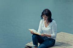 Книга чтения женщины на таблице доски около озера Стоковое фото RF