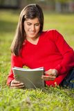 Книга чтения женщины на траве на университетском кампусе Стоковое Изображение RF
