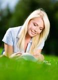 Книга чтения женщины на траве Стоковая Фотография